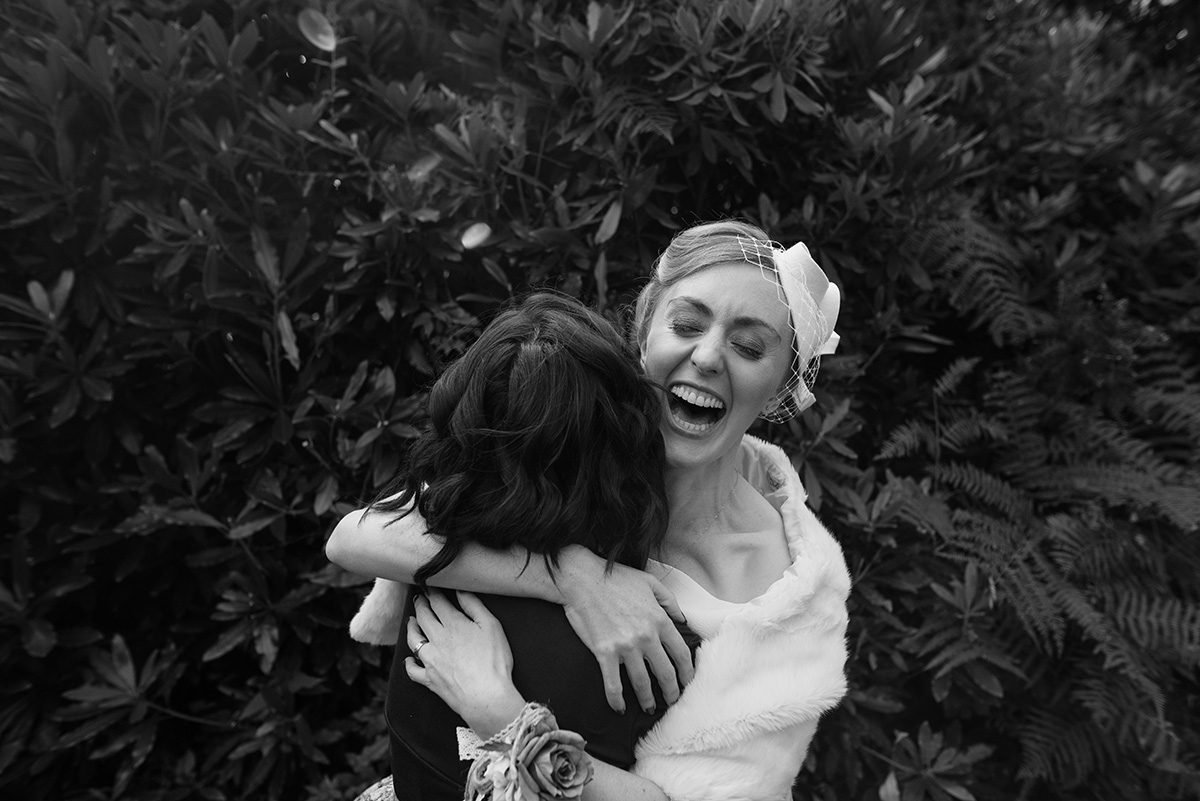 bride laughing and hugging bridesmaid Cork Wedding Photographer