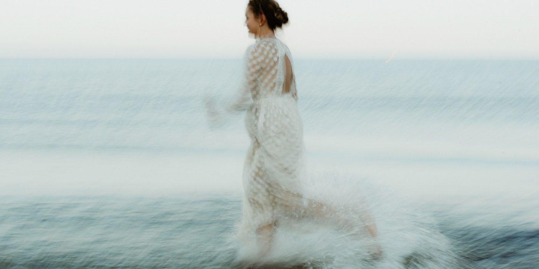 bride running through water