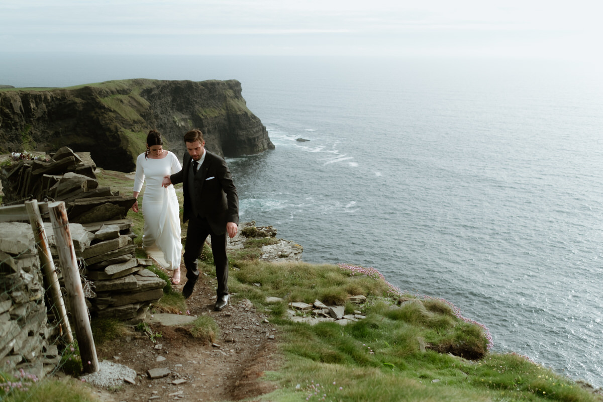bride and groom walking by the cliffs of moher elopement