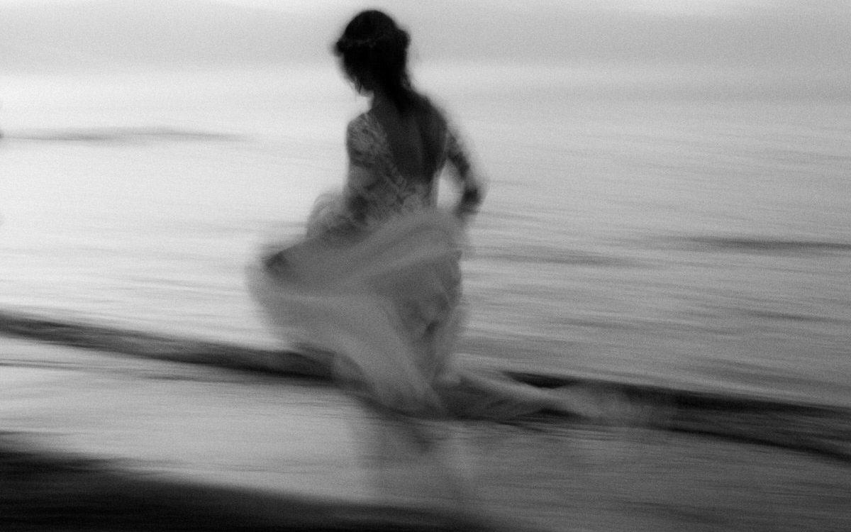bride running barefoot along the beach motion blur documentary wedding photographer northern ireland baltic sea wedding
